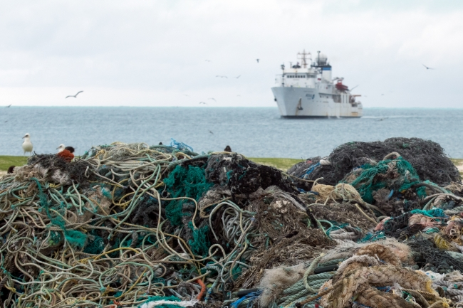 The marine debris pile with the NOAA ship Hi'ialakai in the background.