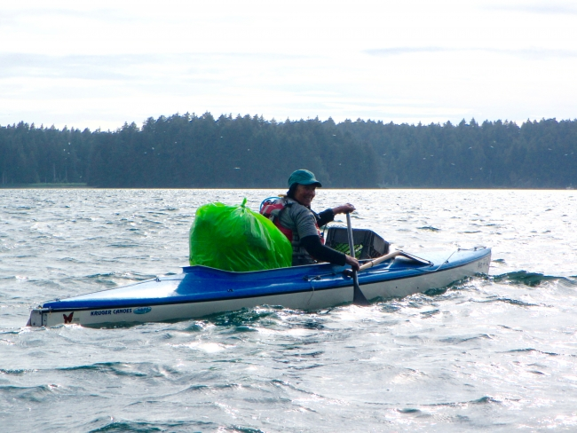 A volunteer on a kayak with a bag of debris.