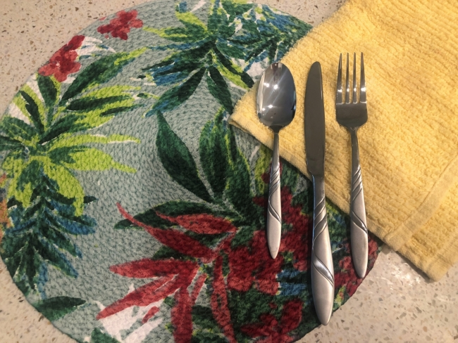 A placemat, utensils, and cloth napkin.
