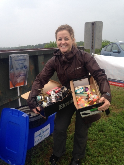 A volunteer holding boxes of collected line and lures.