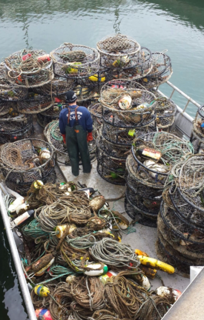 A person standing on a boat, surrounded by lots of derelict crab traps and ropes.