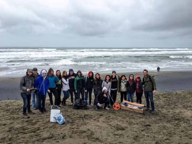 A group of students on a beach with monitoring equipment.