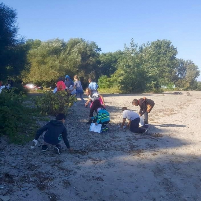 Students cleaning up a beach.