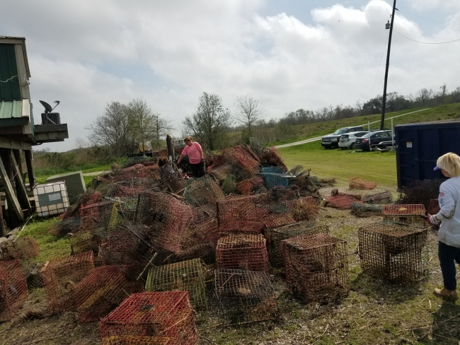 Two people stand to look at a huge pile of collected crab pots.