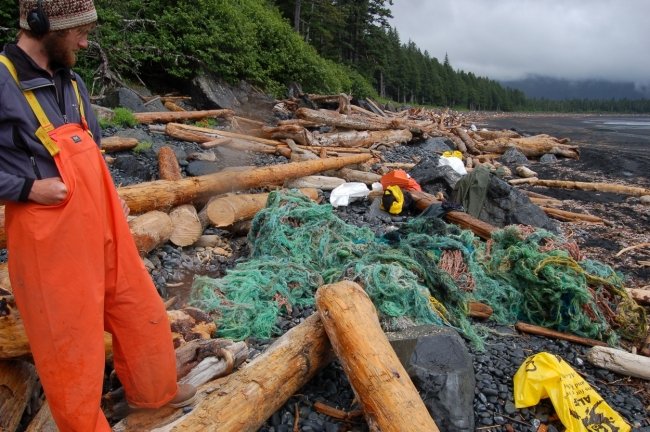 A man looks down on marine debris along a rugged Alaskan beach.