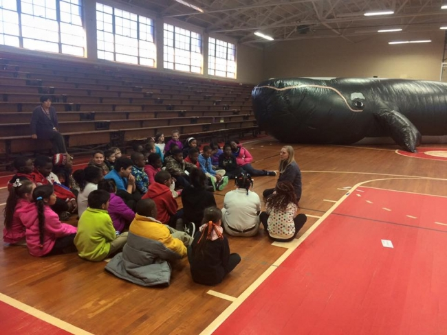 Students sit on the floor with the inflatable whale in the background.