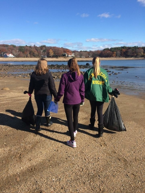 Students picking up trash on a beach.