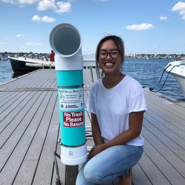 A person poses with a bin on a dock.