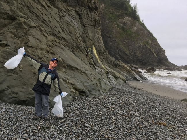 A NOAA team member holds up bags of collected trash from a cleanup.