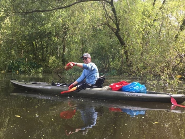 A person paddles a kayak while collecting floating debris.