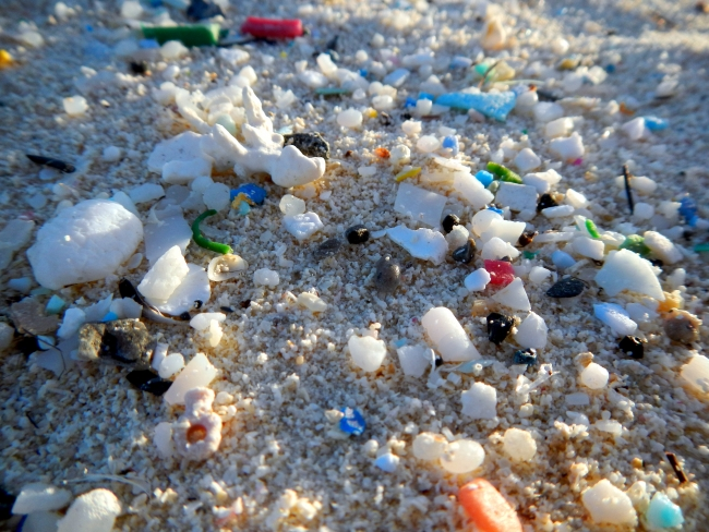 A close up of microplastics on a beach.