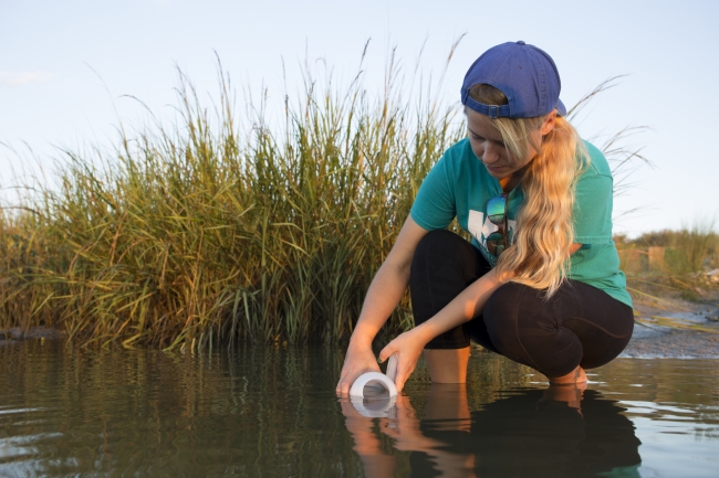 A participant collects a water sample.