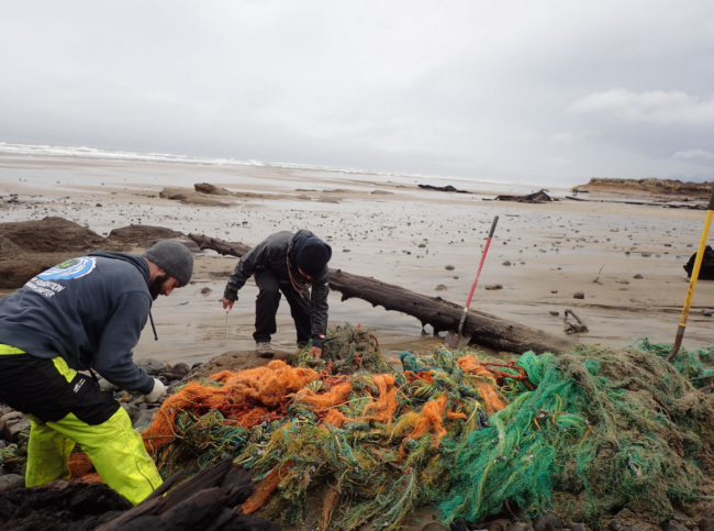 Two people cleaning up nets on a beach.