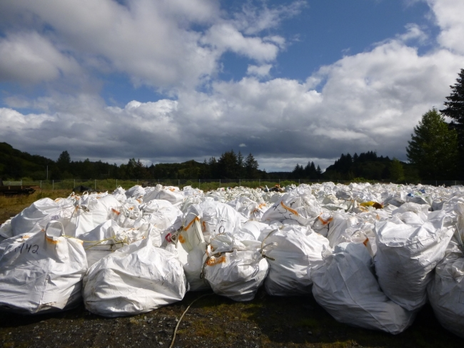 A pile of super sacks (plastic bags) filled with collected debris.