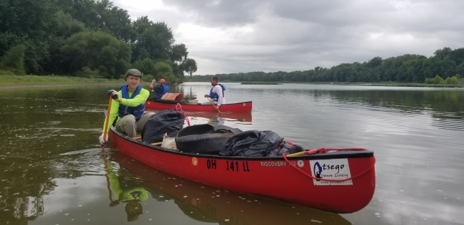 Volunteers paddle in removed marine debris.