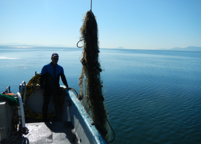A person on a boat standing next to a derelict fishing net.