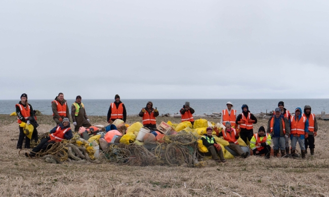 16 people stand around a large pile of collected marine debris and smile for a picture.