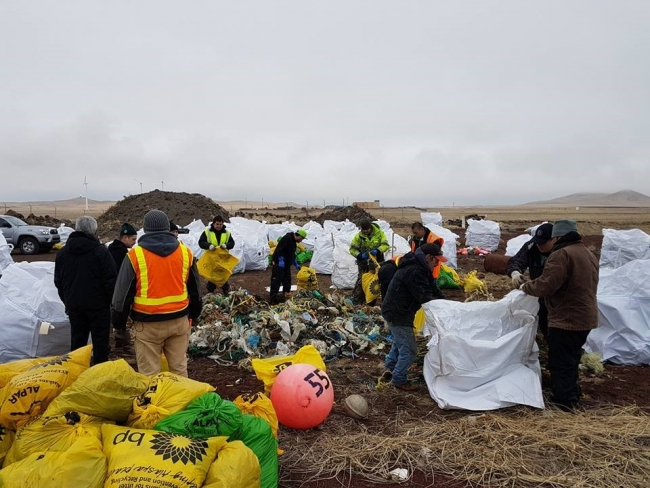 Several people sort marine debris into different piles or load the debris into white bags.