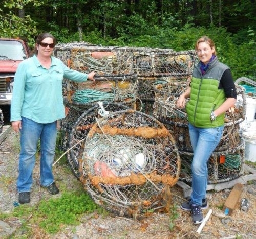 Two people standing next to derelict crab pots.