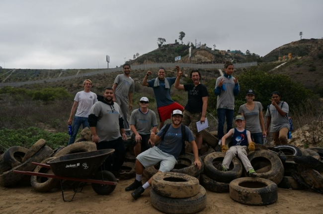 11 people smile for a picture around a large pile of collected tires.