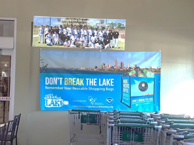 "A sign behind shopping carts reading ""Don't Break the Lake Remember You Reusable Shopping Bags""."