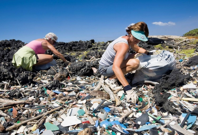 People picking up handfuls of small plastic debris from a beach.