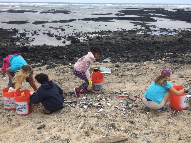 Students picking up debris on a beach.