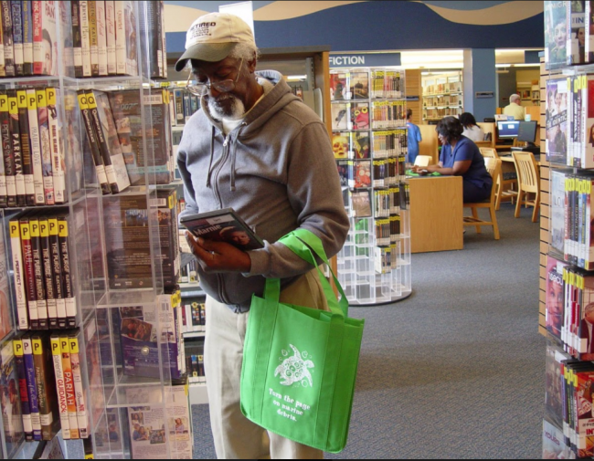 A man with a reusable bag browsing in the library.