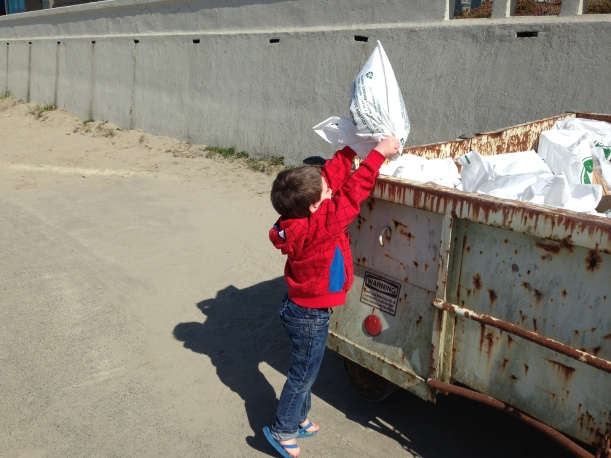 A young child putting a bag of trash into a dumpster.