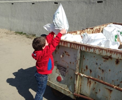 A child putting a bag of trash into a dumpster.