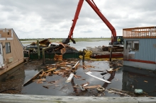 A crane moving floating debris into a floating dumpster.