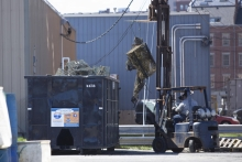 A person uses a forklift to place old fishing nets into a dumpster.