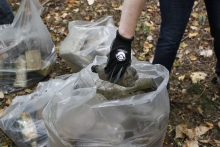 A person putting a collected plastic bottle into a bag of other debris.