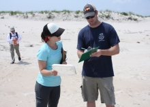 A woman holding a white plastic lid stands on a beach next to a man writing on a clipboard.