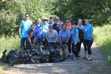 Volunteers stand behind several full garbage bags of collected debris.