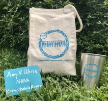 A reusable cotton lunch bag, wooden name tag, and metal cup.
