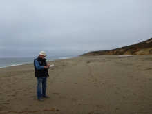 Man stands on a beach recording data on a clipboard.