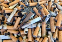 Pile of cigarette butts on a beach.