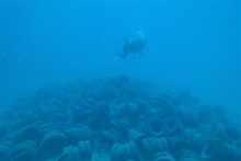A SCUBA diver swims over a pile of tires located on the ocean floor near Hawaii.