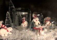 Three glass jars contain white toy bears and are set on fake snow.