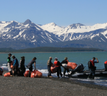 A cleanup crew moving debris into a boat with snowy mountain in the background.