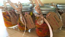 Seven glass jars are filled with sliced peppers and tied with a bow, affixed with a paper tag.