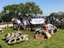 "People hold up a sign reading ""The Ghost Trap Rodeo Event Series"" behind piles of marine debris and tires."