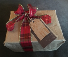 A present wrapped in brown paper bag and reusable fabric ribbon.