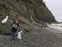A beach cleanup volunteer holds bags of trash up in the air.