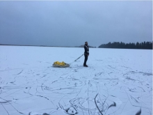 A person stands on a frozen lake pulling a yellow sled.