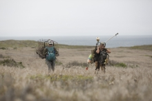 Man and woman carry debris through an open field.