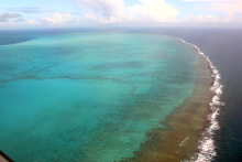 The Northwestern Hawaiian Islands are mostly uninhabited, but still highly afflicted by marine debris. Here, an aerial image shows Midway Atoll's barrier reef. (Photo Credit: NOAA PIFSC, Coral Reef Ecosystem Program)