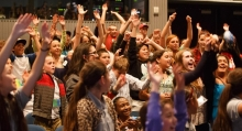 Students raise their hands at a plastic pollution summit at Monterey Bay Aquarium