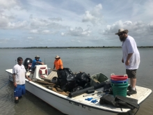 The four person field crew of commercial watermen on a boat full of collected marine debris.